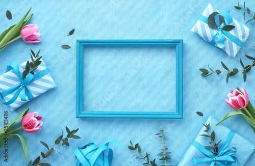 Blue background with wrapped gift boxes and eucalyptus twigs around empty wooden frame