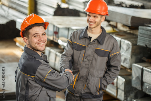 View from above of two cheerful in uniform and helmets shaking hands on metal stock. Happy male worker turning to camera, posing and smiling, his colleague looking at him. Concept of collaboration.