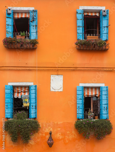 Orange wall with windows and flowers on window sills, Burano, Italy