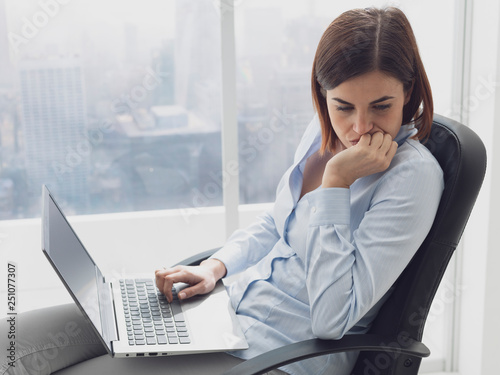 obraz lub plakat Pensive businesswoman working with her laptop