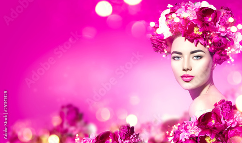 Leinwandbild Motiv Flowers hairstyle. Beauty model girl with pink peony flowers wreath over purple background