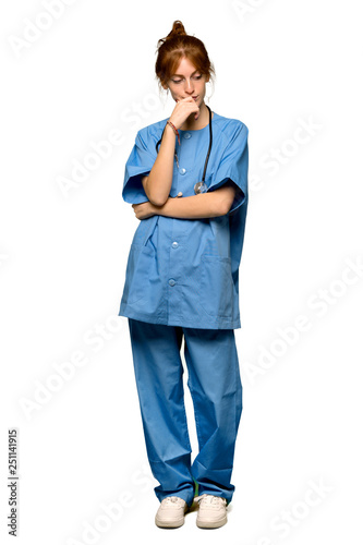 6f4222736af A full-length shot of a Young redhead nurse looking down with the hand on