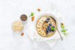 Leinwanddruck Bild - Healthy vegetarian food, oatmeal with fresh blueberry, banana, almond nuts and chia seeds for breakfast, view from above