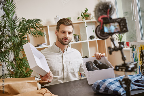 Fashion blog. Smiling male blogger opening box with sneakers while recording new video at home on a digital camera.