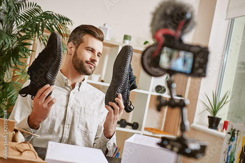 Popular fashion blogger. Young male fashion blogger holding stylish sneakers while making new content for his fashion blog.