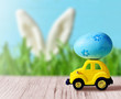 Retro toy car with Easter egg on the roof on spring background. Easter concept.