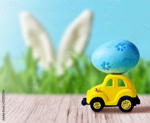 Retro toy car with Easter egg on the roof on spring background. Easter concept. - 251170786