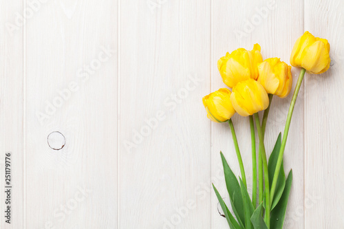 Yellow tulips on wooden table - 251179776