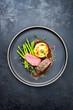 Leinwanddruck Bild - Traditionell gegrillter Rehrücken mit grünen Spargel, gebratenen Kartoffel Püree und Kräuter in brauner Rotwein Sauce als Draufsicht auf einem Modern Design Teller mit Textfreiraum