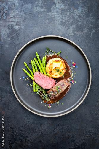 Leinwanddruck Bild Traditionell gegrillter Rehrücken mit grünen Spargel, gebratenen Kartoffel Püree und Kräuter in brauner Rotwein Sauce als Draufsicht auf einem Modern Design Teller mit Textfreiraum