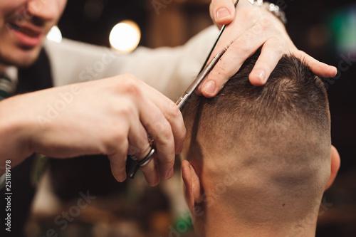 Professional haircut with scissor in a male barbershop salon