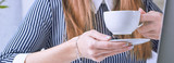 Coffee cup in businesswoman's hand. Young woman working with documents and laptop close-up.
