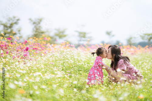 Mother and her baby girl kissing in cosmos meadow - 251218329