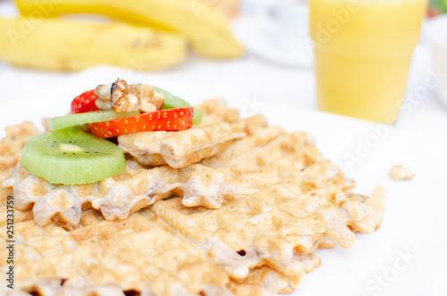 Desayuno saludable - waffles de harina del negrito, servidos con nueces, kiwi, fresas, banana y jugo fresco - 251233759
