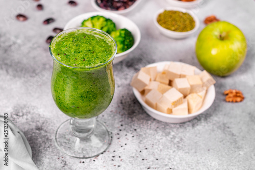 Ginger green apple smoothie on concrete background. It can be used as a background © chernikovatv