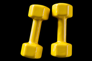 Two yellow dumbbells on a black background © fotosr52