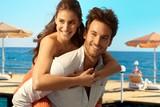 Happy couple playing piggyback at seaside beach