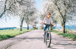 Leinwandbild Motiv Happy smiling woman rides a bicycle on the country road under blossom trees. Spring is comming concept image.