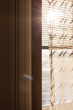 Plastic window with blinds and curtains with rays of sun