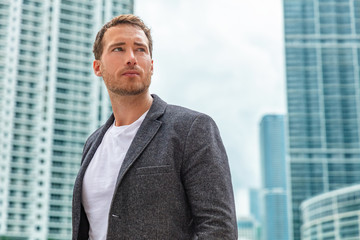 Businessman young man serious portrait wearing smart casual blazer outdoor in city high-rise buildings background.