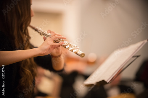 A young woman playing flute at the concert
