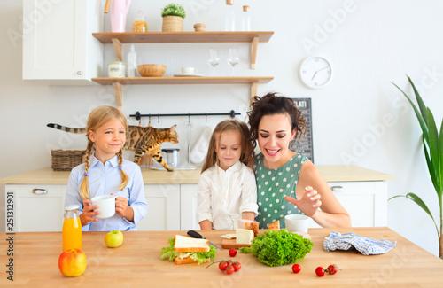 Leinwandbild Motiv Happy young brunette mother with cute little kids having breakfast