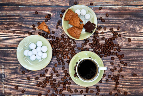 Cup of coffee, coffee beans, chocolate, cranberry in sugar and almond cookies on the saucers. All on the wood boards. Top view © Sergey Yurchenko
