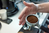 Barista presses ground coffee in the spoon