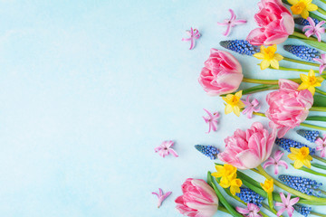 Colorful beautiful spring flowers on pastel table top view. Greeting card for International Women Day. Flat lay.