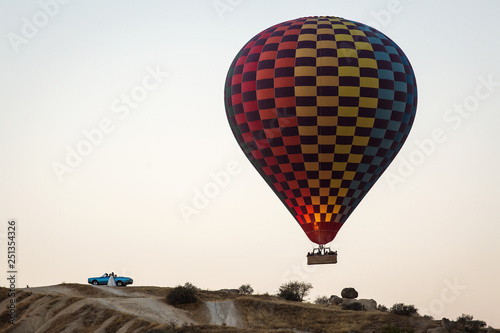 Colorful hot air balloons and an old blue car in Cappadocia.