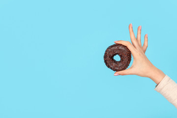 Hand holding delicious chocolate doughnut