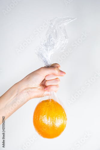 Excessive plastic use concept: orange in plastic wrap held in a hand. Unreasonably over-packaged food products: person holds fresh fruit in kitchen wrap - 251362962
