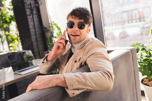 selective focus of trendy man in sunglasses talking on smartphone near laptop in cafe