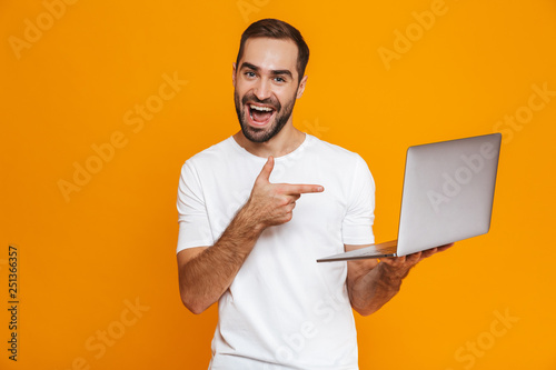 Portrait of handsome man 30s in white t-shirt holding silver laptop, isolated over yellow background