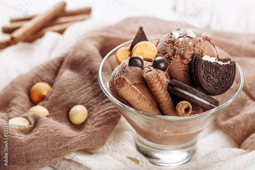 Leinwanddruck Bild Chocolate Ice Cream Dessert Bowl with Cookie Snack. Cold Delicious Brown Icecream Ball and Biscuit on Wooden Background. Cocoa Gelato Serving Closeup Banner. Traditional Coffee Pastry Cuisine