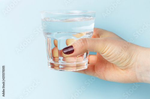 Female hand holding a glass with water, blue background © TATIANA