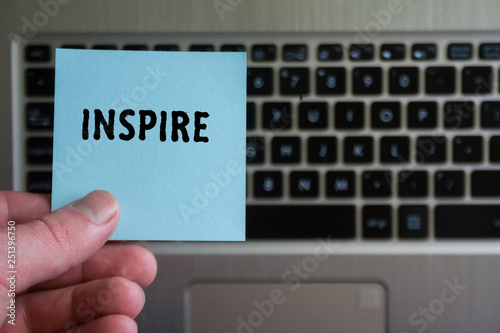word INSPIRE on sticky note hold in hand on laptop keyboard background.