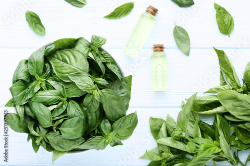 Bottles of essential oil with basil leafs in bowl on wooden table - 251397963