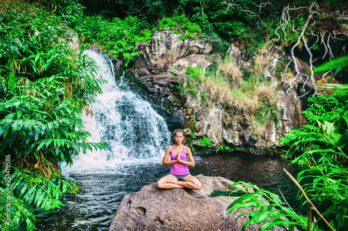 Yoga retreat woman praying doing the lotus pose meditating at waterfall forest in Kauai, Hawaii. Spiritual girl doing meditation in tranquil serenity nature. Tropical travel destination. - 251419586
