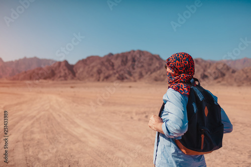 Tourist man with backpack wearing scarf on head. Happy traveler admiring Sinai Desert and mountains - 251433989