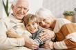 Happy grandparents hugging their grandson