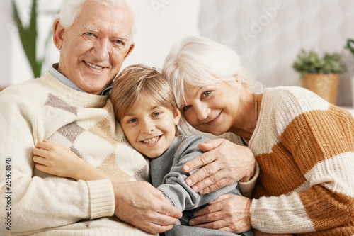 Happy grandparents hugging their grandson