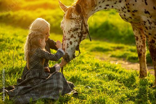 Leinwandbild Motiv mother with a little girl in dresses stroke a spotted horse