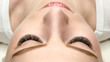 Female face with eyelash extensions, well groomed skin, top view, close up, selective focus