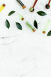 Tea tree oil in small glass bottle near fresh tea tree leaves on white stone background top view space for text border