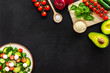 Ingredients for fresh salad. Vegetables, greens, spices, plate of salad on black background top view space for text