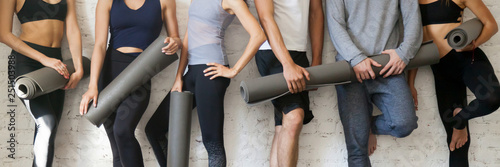 Leinwanddruck Bild Group people wearing activewear holding yoga mats standing near wall