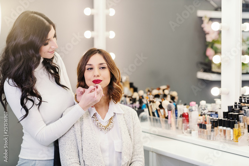 Beautiful caucasian brunette sitting in beauty salon while makeup artist putting red lipstick on her lips.