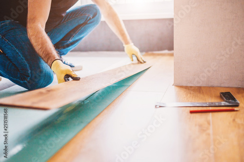 Man at home laying laminate flooring - finishing - 251518568