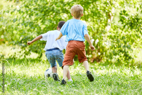 Two sporty boys playing football